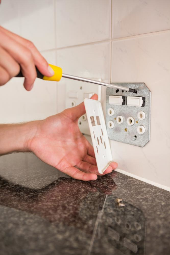 Screwdriver detaching an outlet cover to access wiring